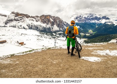 Cyclists standing backwards and watching at beautiful Dolomites mountains covered with snow in South Tyrol, Italy. Alpine activities, mountainbing with amazing nature view