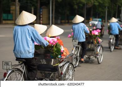 Cyclo (pedicab) driver wears conical hat on Hanoi street
