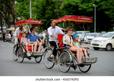 Cyclo and tourists are enjoying the beauty of the Hoan Kiem lake and Hanoi old quarter, Vietnam on a summer day, July 7, 2016.