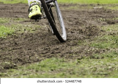 Cyclocross bicycle race through mud, grass, barriers and asphalt