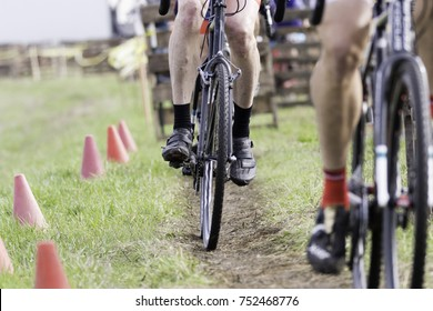 Cyclocross bicycle racers peddling down dirt path