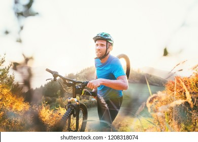Cyclo-cross competition member Man mountain biker carrying his bike up on hill top