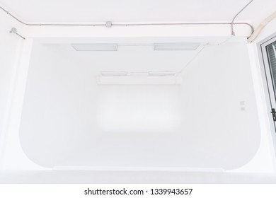 Cyclorama slope room with white painted wall and white floor used for a photo studio, right hand side has a window, is a room suitable for professional photographers and amateurs.
