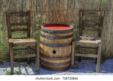 Cylindrical Barrel. Vintage barrel table with two wooden chairs .