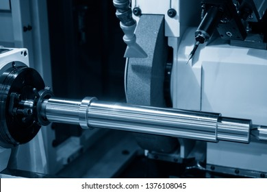The cylindrical grinding machine in the light blue scene with the steel shaft.The automotive part manufacturing process.