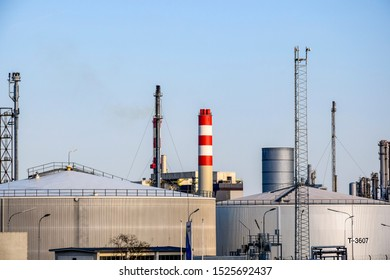 Cylindrical oil storage tanks. Industrial Zone. Towers and pipes against the blue sky. Close-up. Selective focus. Copy space.