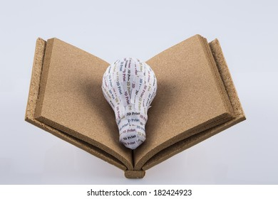 CYMK 3D Printing concept: lightbulb on blank cork book. 3d printers are home devices that allow to bring life to concept and design ideas from paper to phisical prototypes trducing costs and times