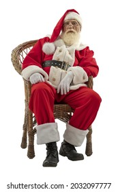 Cynical, serious, indifferent Santa Claus on white background isolated. Senior male actor old man with a real white beard in the role of Father Christmas sitting in a wicker willow chair.