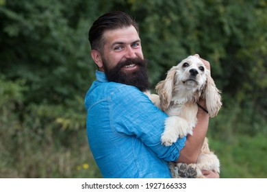 Cynologist concept. Man with Cocker Spaniel in dog park outdoors. Man with puppy - Shutterstock ID 1927166333