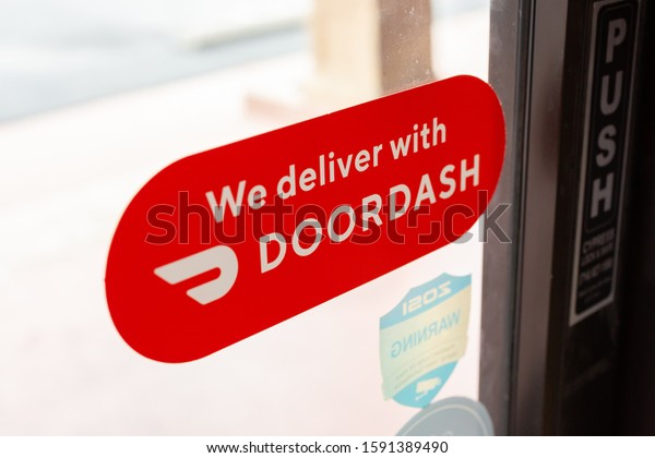 Cypress, California/United States - 11/30/2019: A view of a window sticker that advertises a local restaurant provides food delivery through DoorDash.