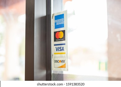 Cypress, California/United States - 11/30/2019: A window sticker of several credit card brands accepted at a local restaurant.