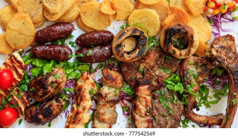 Cypriot delicacies. Mixed grilled meat with vegetables and potatoes on white surface. Close up view.