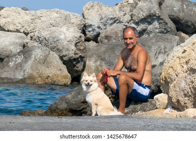 CYPRUS, KARAVAS, ALSANCAK - JUNE 10, 2019: Adult male Cypriot sitting with a cute spitz dog on background of the sea and rocks on Camelot Beach.