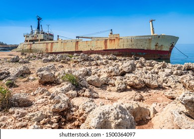 Cyprus. Pathos. View from the shore to an abandoned ship. White stone. Mediterranean coast. Rusty ship on the rocks. The ship ran aground near the shore. Tourist attraction of Cyprus.