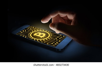 Cyptocurrency or digital money concept image.Bitcoin sign and electrical circuit icon on smartphone screen and finger point to phone screen .Fintech Investment Financial Internet Technology Concept.