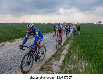 Cysoing, France - April 14, 2019: The winner of the race,Philippe Gilbert, riding in the leaders group on the cobblestone road from Cysoing to Bourghelles during Paris-Roubaix 2019