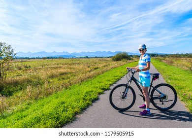 CZARNY DUNAJEC, POLAND - SEP 12, 2018: Young woman with bike on cycling track around Tatra Mountains near Czarny Dunajec village. The end point is in Trstena village in Slovakia.