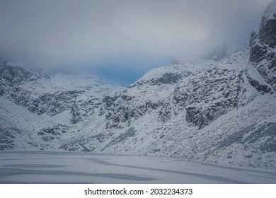 Czarny Staw Gąsienicowy Lake in December, High Tatra Mountains, Poland. Overcast sky, depressing mood, cold wind. Selective focus on the rocks, blurred background. - Shutterstock ID 2032234373