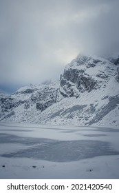 Czarny Staw Gąsienicowy Lake in winter, High Tatra Mountains, Poland. Kościelec Peak in the fog and clouds. Selective focus on the rocks, blurred background. - Shutterstock ID 2021420540