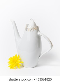 Czech ceramic white teapot and a yellow flower on white background, dating back to the nineteenth sixties