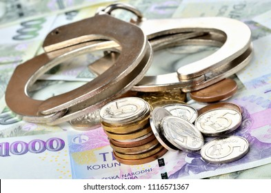 Czech coins and police handcuffs on banknotes