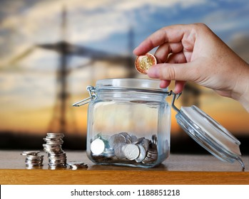 Czech crown coins in a glass moneybox - savings for electricity and energy costs - hand holding a coin