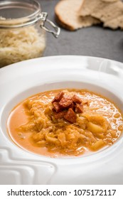 Czech cuisine sauerkraut soup with sausage and potatoes in white dish on blask stone table