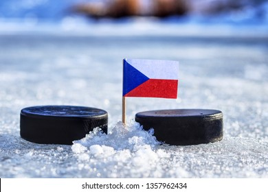 Czech flag on toothpick between two hockey pucks on ice in outdoor. Winter classic. Flag on frozen pond on unkempt ice. Old ice hockey style.