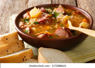 Czech food: Zelnacka cabbage soup with sausages and vegetables close-up in a bowl on the table. horizontal