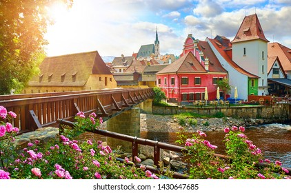 Czech Krumlov, (Cesky Krumlov), Czech Republic. Wooden bridge over river Vltava. Vintage picturesque old town with colorful houses and chapel of church. Rose flowers on bank. Sunny summer day.