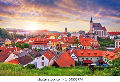 Czech Krumlov, Czech Republic. Scenic Panorama of old town with view at roofs of houses and saint vitus cathedral. Evening sunset landscape. Sky with sunlight and clouds.