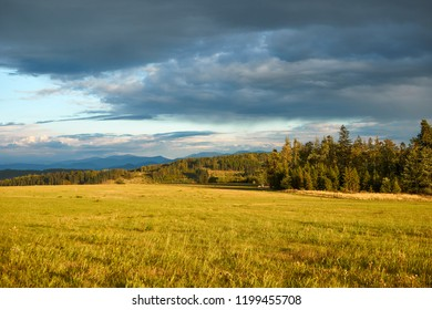 Czech landscape at sunset, Beskydy mountain in the distance, dark clouds on the sky