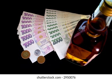 Czech money and whiskey bottle on black background