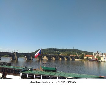 Czech national flag on a trip boat in the front. Charles bridge and Lesser Town of Prague and Petřín tower on the hill in the back. Blue sky, summer vacation.