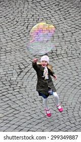 CZECH ,PRAGUE â??MARCH 7: Unidentified girl trying to catch bubble on March 7 2015 in Prague,Czech Republic.