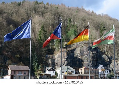 Hřensko, Czech Republic, 02-18-2020, different flags in the wind in Hrensko, Czech Republic, a small town near to the German border located at the Elbe river