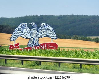 Czech Republic - June, 2018: Logo of Mattoni, Carlsbad mineral water company, giant eagle on the field. View from the road