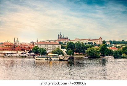 Czech Republic, Prague -28 Jule 2016: Scenic view of tree lined promenade along river in lovely European city as boat passes nearby