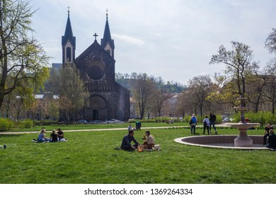 Czech Republic, Prague, April 13, 2019: group of people relaxing on lush green grass and enjoying early spring day on Karlinske namesti square park with gothic church and trees, blue sky background