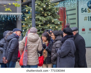 Czech republic, Prague, old town, December 6, 2017: group of tourist standing and talking in front of decorated christmas tree in old prague center narodni trida
