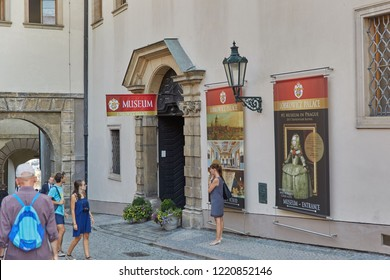 CZECH REPUBLIC, PRAGUE - SEPTEMBER 13, 2016: People walk near the sign above the entrance to the museum over the wooden doors of Prague, the Czech Republic.