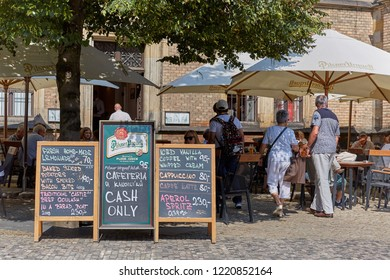 CZECH REPUBLIC, PRAGUE - SEPTEMBER 13, 2016: Wooden shildy on legs with the indication of the prices for food and coffee are near the cafe in Prague, Czech Republic.
