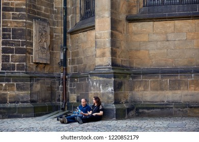 CZECH REPUBLIC, PRAGUE - SEPTEMBER 13, 2016: A man and a woman are sitting on a paving stone near the wall of a building in a street in Prague, Czech Republic.