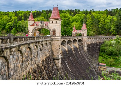 Czech republic, Talsperre Les Kralovstvi (Forest Kingdom) - May 15, 2021. Historic hydraulic water dam with orange water in river Elbe