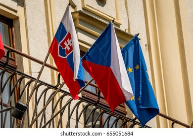 Czech, slovak and europe flags in wing on a balcony of hotel
