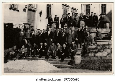 THE CZECHOSLOVAK REPUBLIC - CIRCA 1950s: Vintage photo shows a big group of men stand in front of historic building. Antique black & white photography.