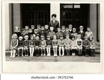 THE CZECHOSLOVAK SOCIALIST REPUBLIC - 1968: Vintage photo shows pupils (schoolmates) pose in front of school. Black & white antique photo.