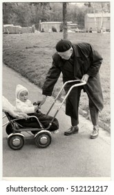THE CZECHOSLOVAK SOCIALIST REPUBLIC - CIRCA 1950s: Vintage photo shows grandfather with a small baby in the pram (carriage). Retro black & white  photography