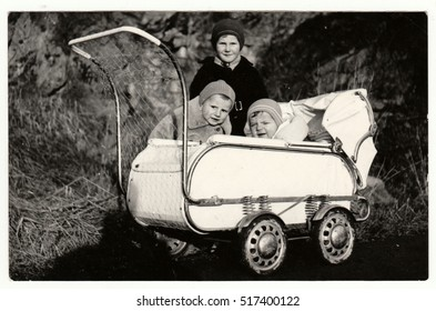 THE CZECHOSLOVAK SOCIALIST REPUBLIC - CIRCA 1950s: Vintage photo shows  small children and baby in the pram (carriage) in the wintertime. Retro black & white  photography.