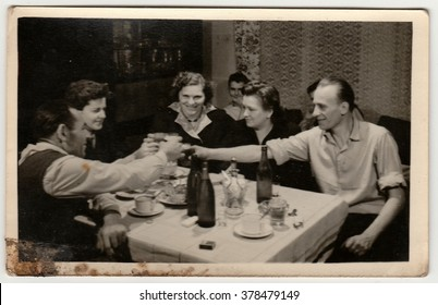 THE CZECHOSLOVAK SOCIALIST REPUBLIC - CIRCA 1960s:  Vintage photo shows women and men propose a toast. Photo has dirt as it has been found in loft.